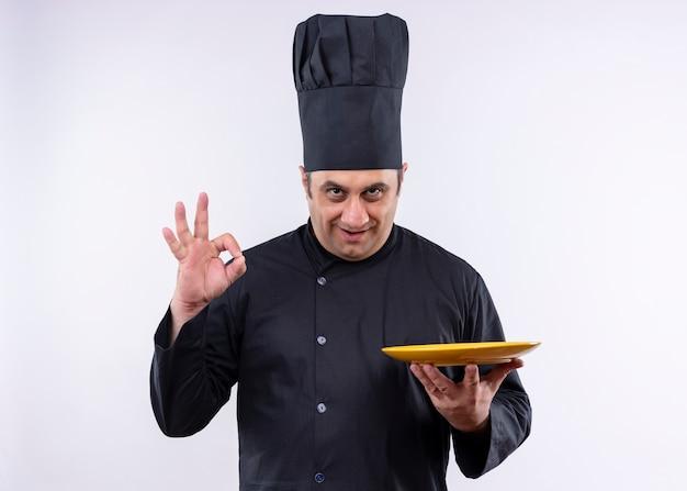 Cozinheiro chef masculino vestindo uniforme preto e chapéu de cozinheiro segurando um prato sorrindo, mostrando uma placa de ok em pé sobre um fundo branco