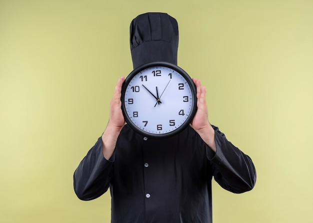 Cozinheiro chef masculino vestindo uniforme preto e chapéu de cozinheiro segurando um relógio de parede, escondendo o rosto atrás dele, em pé sobre um fundo verde