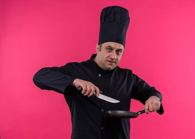 Cozinheiro chef masculino vestindo uniforme preto e chapéu de cozinheiro segurando uma panela e uma faca, olhando para a câmera com uma cara séria em pé sobre um fundo rosa