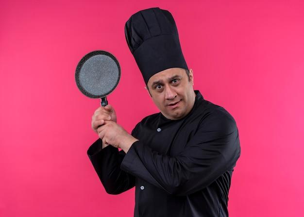 Cozinheiro chef masculino vestindo uniforme preto e chapéu de cozinheiro segurando uma panela, olhando para a câmera confuso em pé sobre um fundo rosa