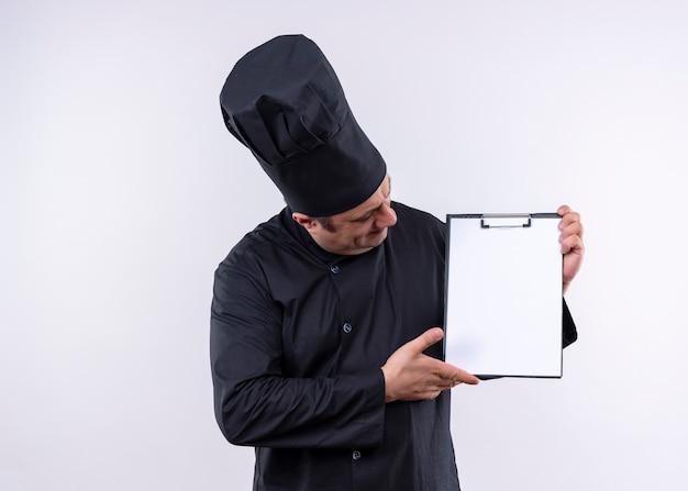 Cozinheiro chef masculino vestindo uniforme preto e chapéu de cozinheiro segurando uma prancheta com páginas em branco olhando para ela em pé sobre um fundo branco