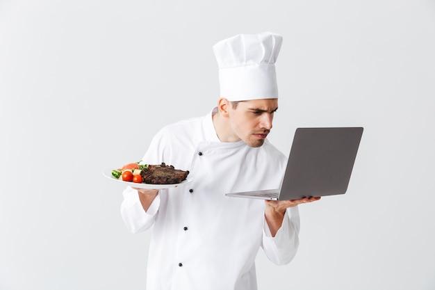 Cozinheiro chef sério vestindo uniforme em pé sobre uma parede branca, segurando um laptop, mostrando um prato