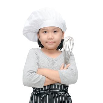 Cozinheiro chefe asiático feliz da menina que guarda utensílios de cozimento e sorriso isolado no fundo branco, imagem quadrada.