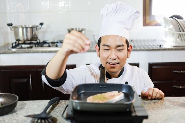 Cozinheiro chefe asiático que cozinha no restaurante da cozinha
