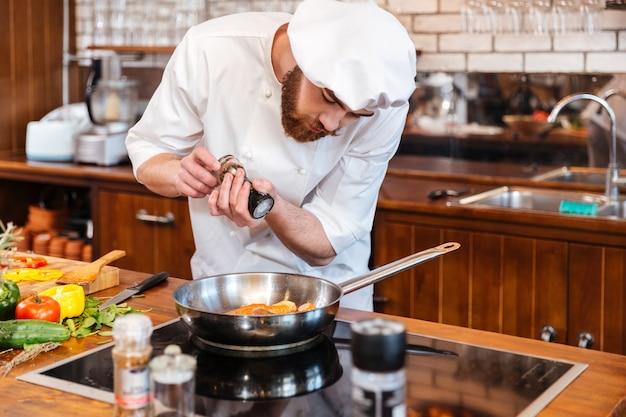 Cozinheiro chefe bonito concentrado cozinhando bife de salmão na frigideira e cortando salada de legumes na cozinha