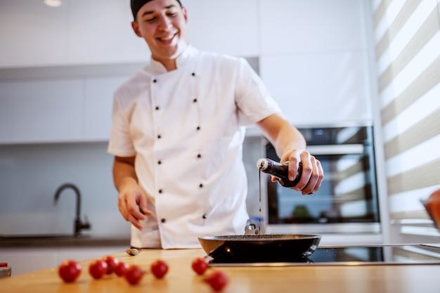 Cozinheiro chefe caucasiano de sorriso feliz considerável no uniforme que está na cozinha e que adiciona a especiaria na massa. cozinha italiana.