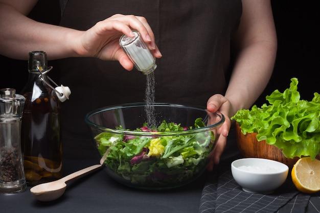 Cozinheiro chefe da mulher na cozinha que prepara a salada vegetal.