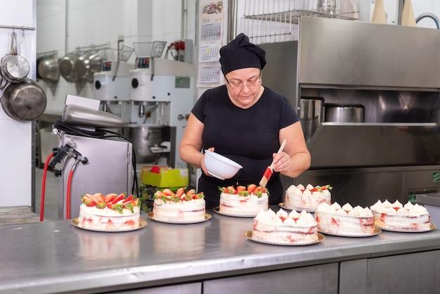 Cozinheiro chefe de pastelaria da mulher que sorri e que trabalha feliz, fazendo bolos na loja de pastelaria.