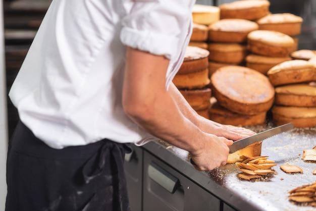 Cozinheiro chefe de pastelaria que corta o bolo de esponja em camadas. processo de produção de bolo.