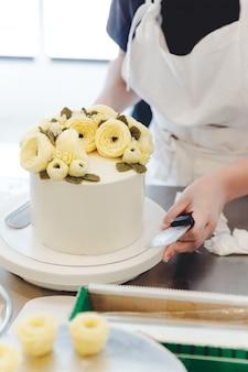 Cozinheiro chefe de pastelaria que faz uma flor amarela da manteiga para a decoração do bolo.