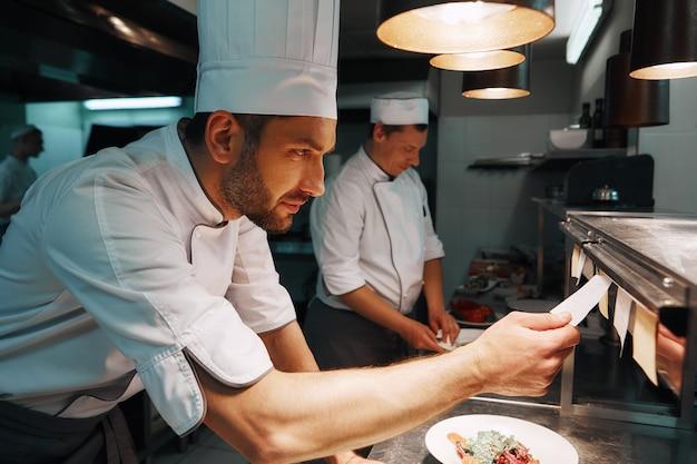 Cozinheiro chefe de serviço incrível verificando os pedidos na cozinha do restaurante