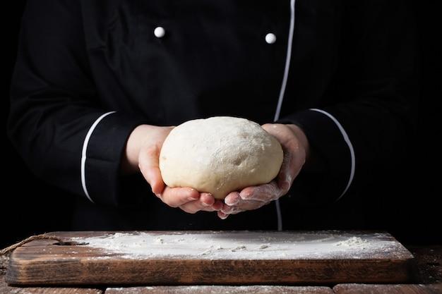 Cozinheiro chefe fêmea que guarda a massa de fermento em suas mãos no fundo preto.