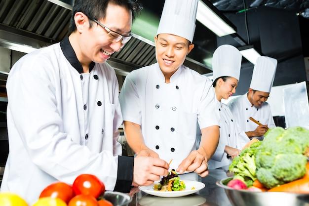 Cozinheiro chefe indonésio asiático junto com outros cozinheiros no restaurante ou na cozinha comercial do hotel que cozinham, terminando o prato ou a placa