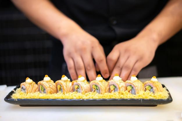 Cozinheiro chefe japonês que faz o sushi no restaurante. comida japonesa tradicional, rolo de sushi de salmão.