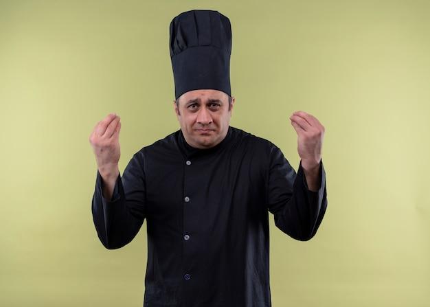 Cozinheiro chefe masculino chateado, vestindo uniforme preto e chapéu de cozinheiro, olhando para a câmera, confuso, gesticulando com as mãos em pé sobre um fundo verde