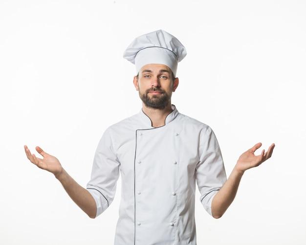 Cozinheiro chefe masculino que está de encontro ao fundo branco que shrugging