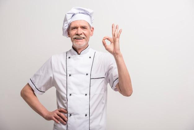 Cozinheiro chefe masculino sênior no uniforme que gesticula o sinal aprovado.