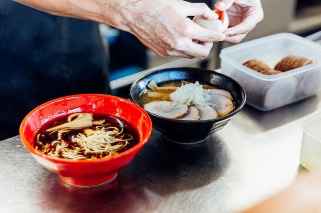 Cozinheiro chefe que adiciona ingredientes no macarronete de ramen para fazer o miso e o ramen do shoyu.