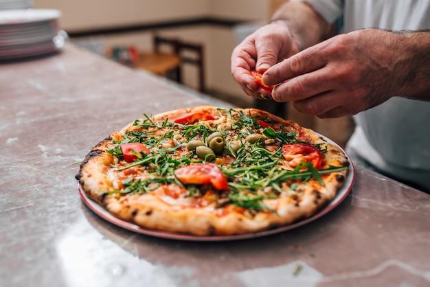 Cozinheiro chefe que adiciona tomates como um toque final na pizza.