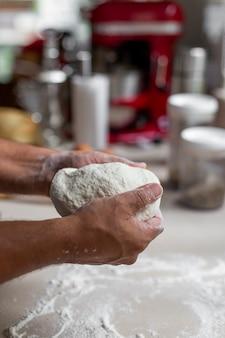 Cozinheiro chefe que amassa a massa fresca para o pão, a massa ou a pizza de cozimento.