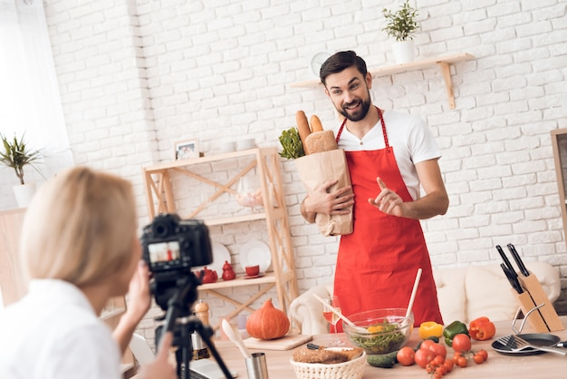 Cozinheiro chefe que apresenta ingrdients do alimento para a câmera culinária do podcast.