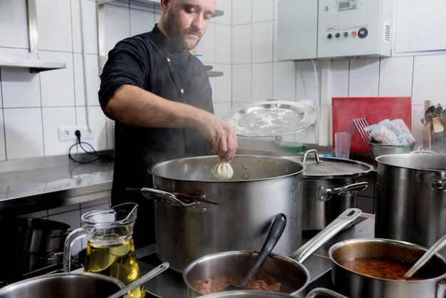 Cozinheiro chefe que coocking o khinkali georgian ou o wonton japonês. refeição tradicional