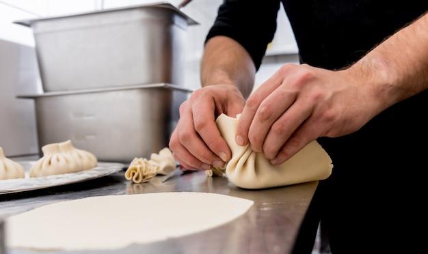 Cozinheiro chefe que coocking o khinkali georgian ou o wonton japonês.
