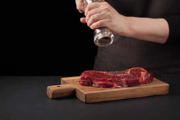 Cozinheiro chefe que cozinha o bife de carne de new york.
