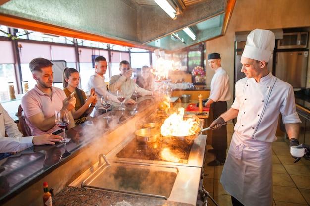 Cozinheiro chefe que cozinha o marisco em um restaurante.