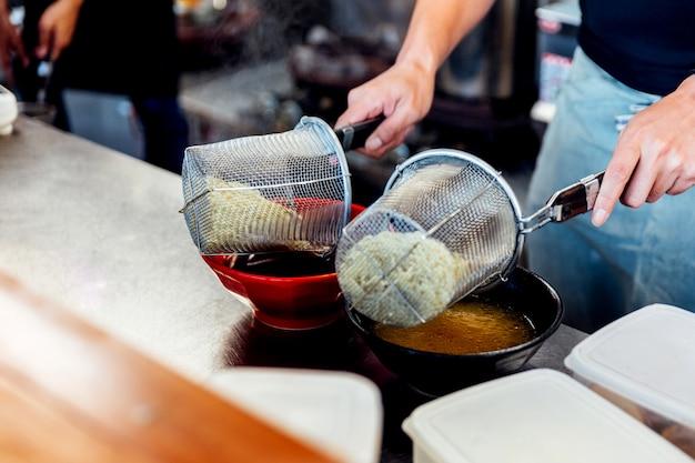 Cozinheiro chefe que ferve o macarronete de ramen na sopa para fazer o miso e os ramen do shoyu.