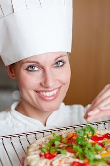 Cozinheiro chefe radiante cozinhar uma pizza
