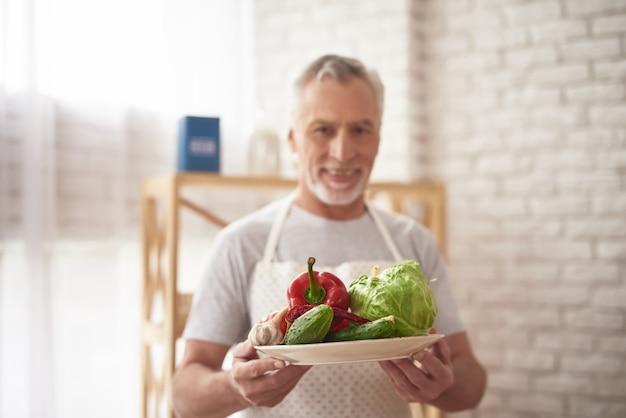 Cozinheiro chefe velho de sorriso cooking. homem segurando vegetais.