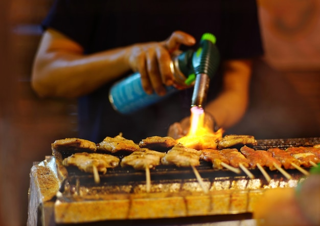 Cozinheiro comerciante queimando fogo para assar espeto de porco, carne do vendedor assada para aquecer na churrasqueira a carvão.