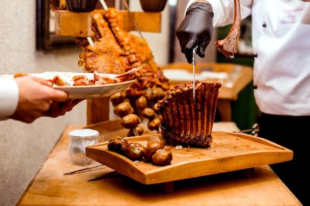 Cozinheiro corta costelas fritas na mesa de corte