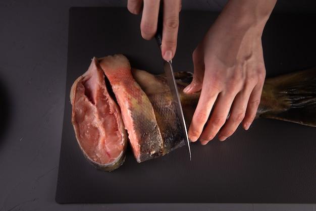 Cozinheiro corta o peixe em pedaços com uma faca em uma placa cinza