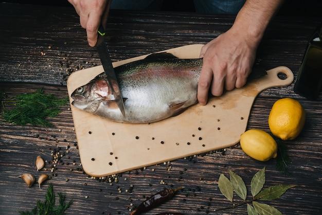 Cozinheiro corta peixe fresco na cozinha, truta crua para cozinhar