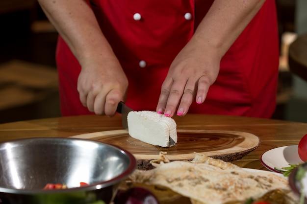 Cozinheiro corta queijo no quadro