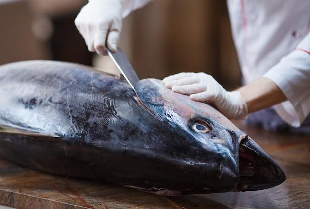 Cozinheiro cozinha atum grande em um restaurante