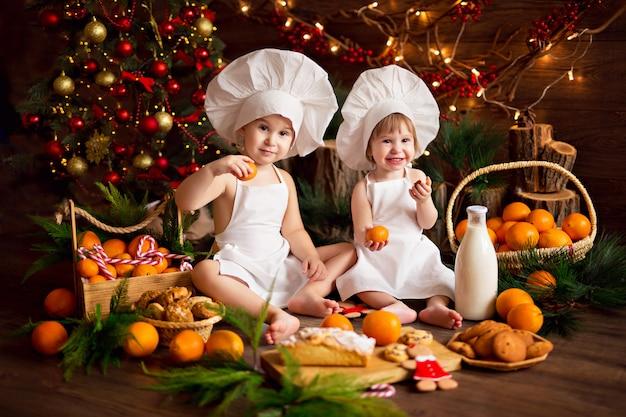 Cozinheiro de bebê preparando biscoitos de gengibre. feliz natal, tangerinas, árvore de natal