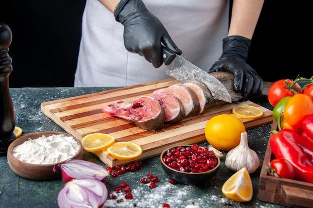 Cozinheiro de frente para o avental cortando peixe cru na tábua de legumes na tábua de madeira na mesa