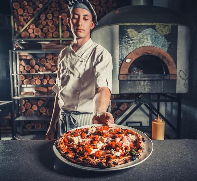 Cozinheiro de homem segurando pizza cozida fresca