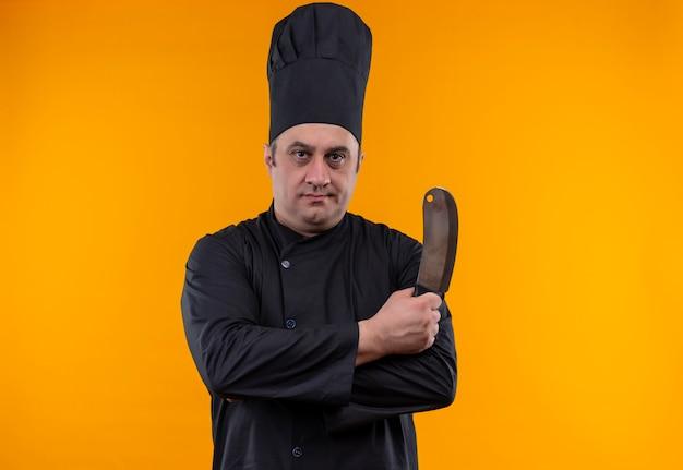 Cozinheiro de meia-idade confiante com uniforme de chef segurando o cutelo na parede amarela com espaço de cópia