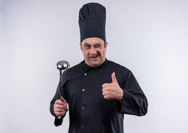 Cozinheiro de meia-idade e piscando em uniforme de chef segurando uma espátula com o polegar na parede branca isolada