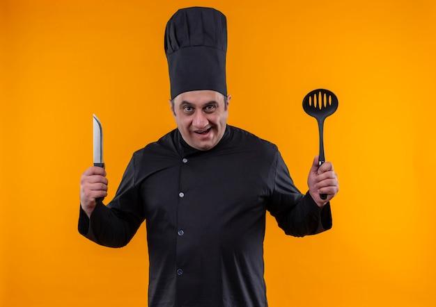 Cozinheiro de meia-idade irritado com uniforme de chef segurando uma concha e uma faca na parede amarela