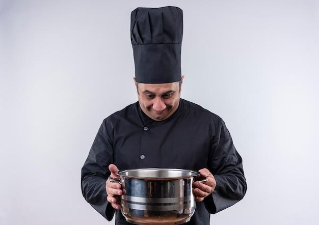 Cozinheiro de meia-idade preocupado com uniforme de chef - em parede branca isolada