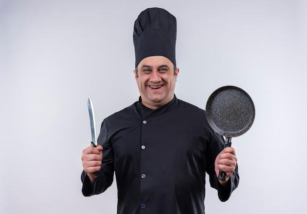 Cozinheiro de meia-idade sorridente com uniforme de chef segurando uma frigideira e um cutelo com espaço de cópia
