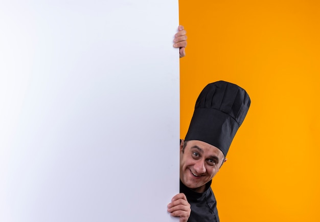 Cozinheiro de meia-idade sorridente com uniforme de chef segurando uma parede branca sobre fundo amarelo com espaço de cópia