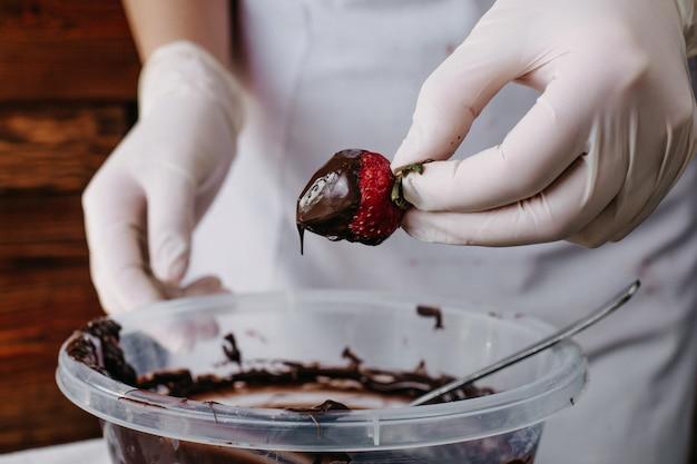 Cozinheiro de morango choco mergulhando morango vermelho dentro de chocolate