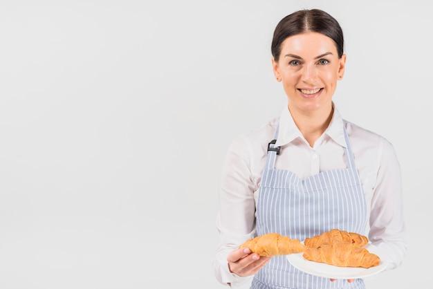 Cozinheiro de pastelaria mulher oferecendo croissant