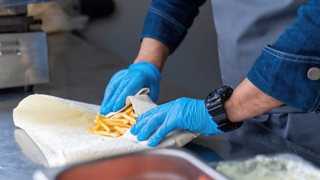 Cozinheiro enrolando um embrulho em um food truck